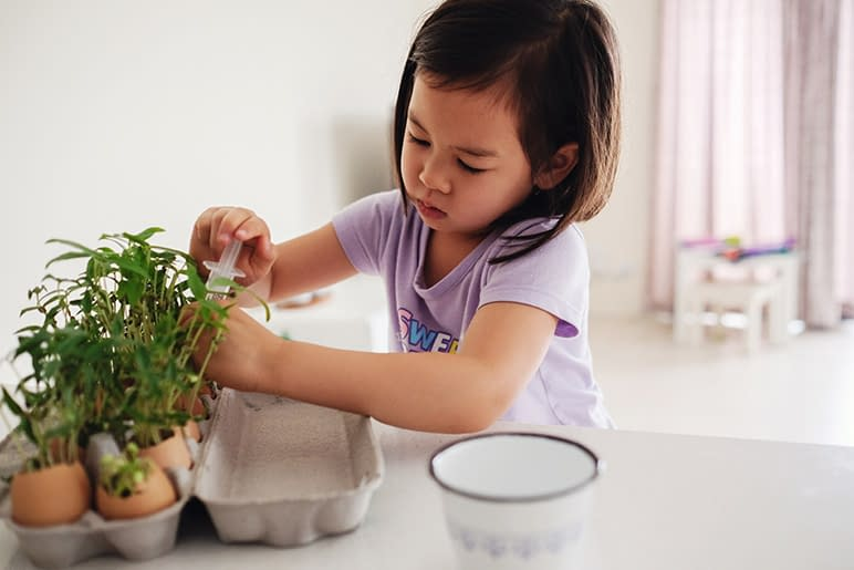 A young girl works on practical life skills in a Montessori classroom.