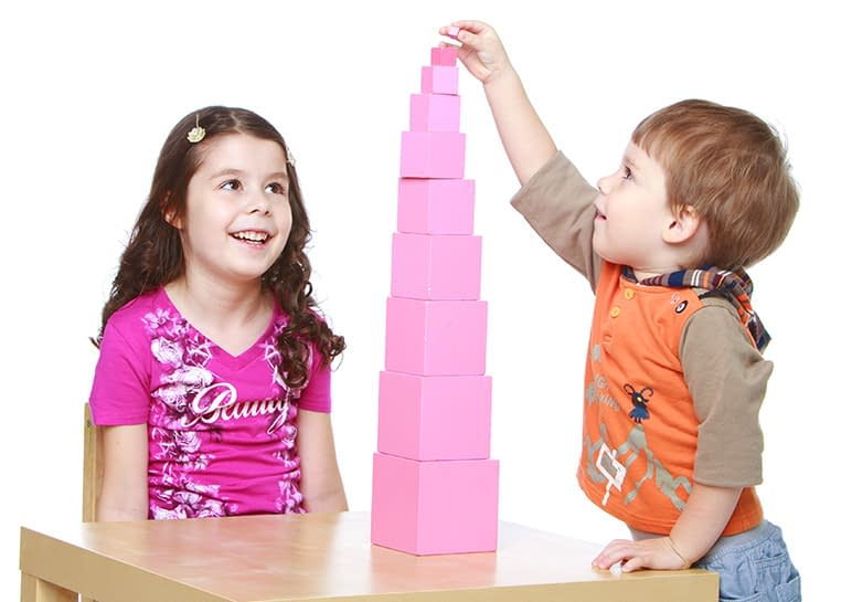 Two preschool age children construct a pink tower in a Montessori classroom.