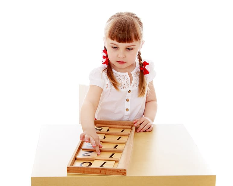 A young girl works on wooden number board in a Montessori classroom.