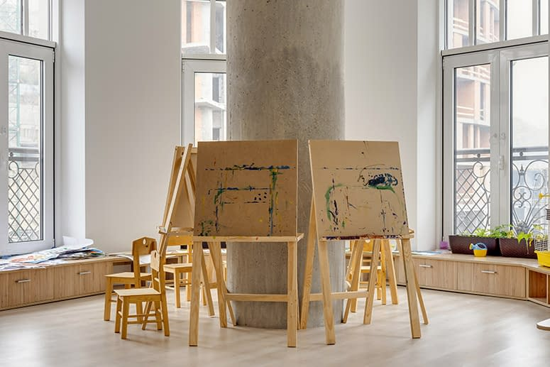 Art easels around a column in a bright room with large art windows, homeschool decore.